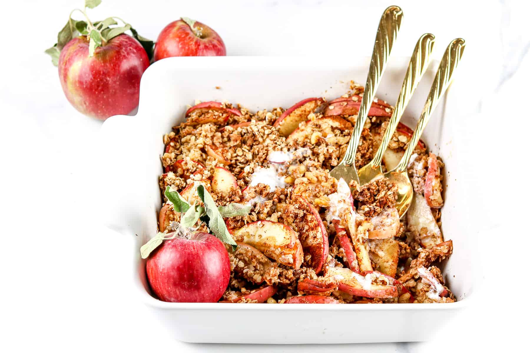 Image of apple crisp in a baking dish with forks.