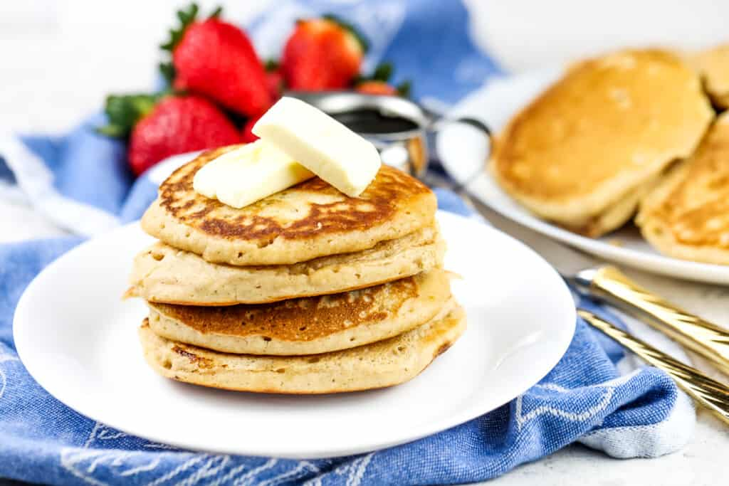 Picture of white plate with stack of brown sugar pancakes with two slabs of butter on top and a gold fork with syrup on the side.