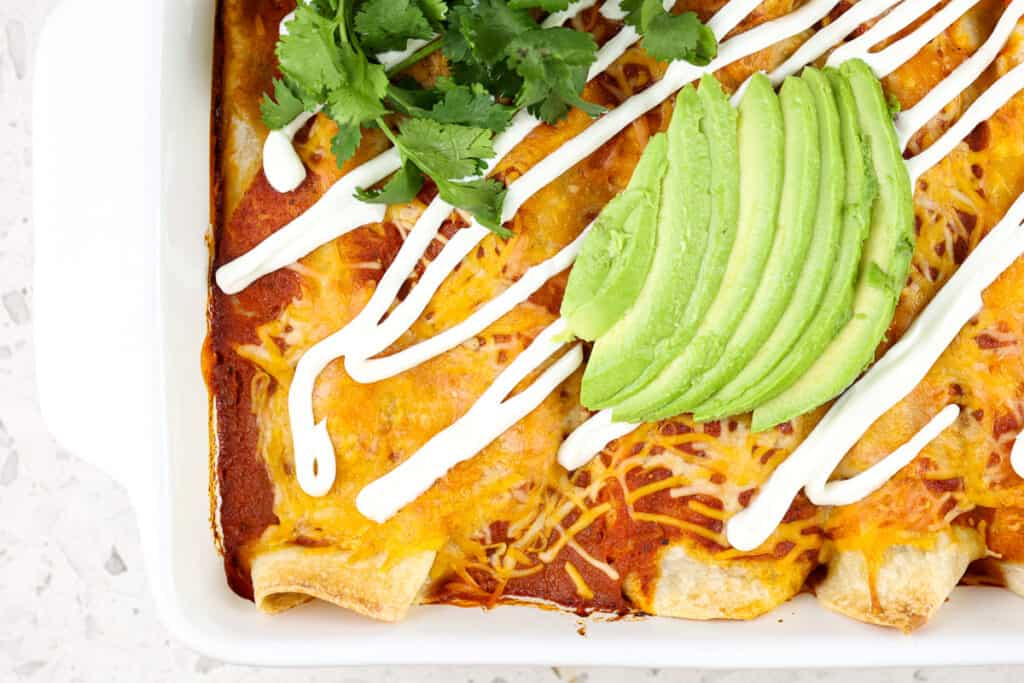 Casserole dish with white brim filled with red sauce enchiladas and topped with green avocado and white sauce drizzle.