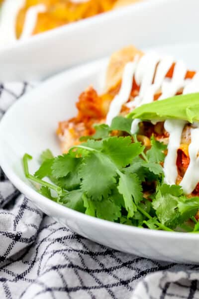 White bowl with red enchiladas and cilantro in it with avocado and white sauce on top, sitting on top of black and white napkin with gold fork.