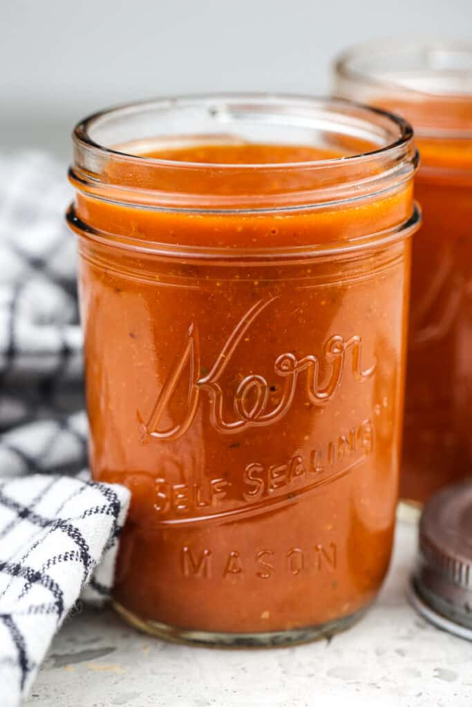 Picture of mason jar holding red enchilada sauce with second jar in the back next to two silver lids and a black towel.