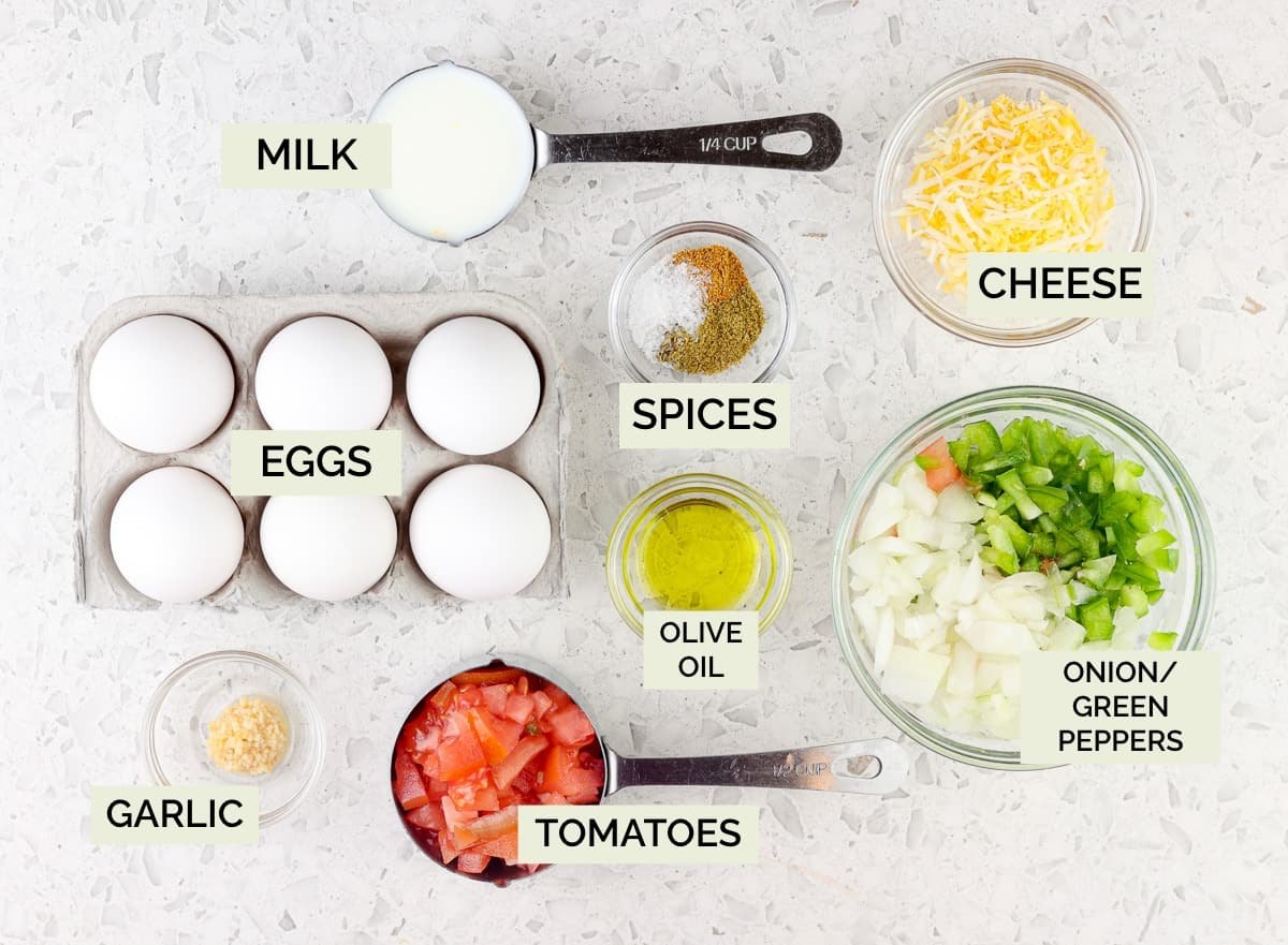 White marble background with picture of eggs, cheese, veggies, and spices in bowls.