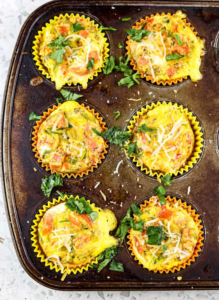 Old rusted muffin tin with 6 veggie and egg frittatas pictured on white marble background.