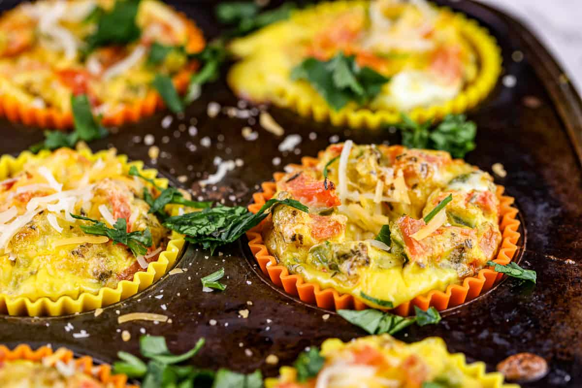 Close up shot of egg frittatas with veggies and cheese on top in a rusted muffin tin.
