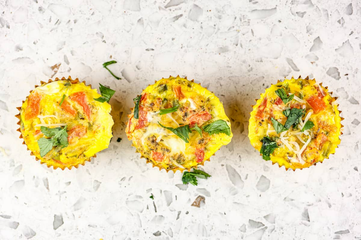Picture of white marble backdrop with 3 veggie frittata muffins in a row.