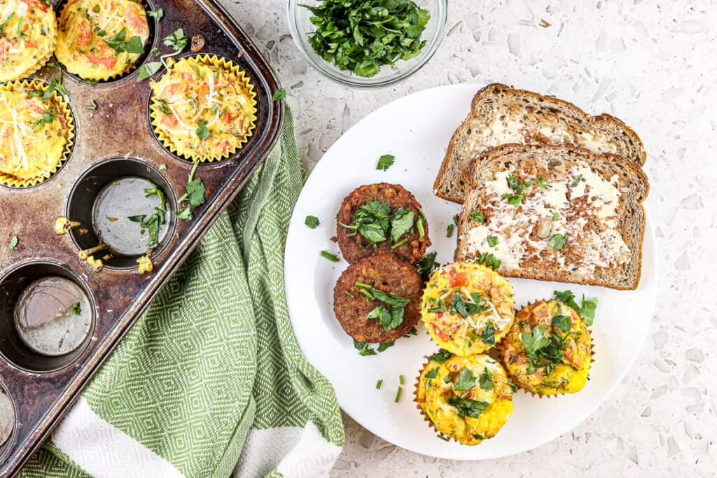 White marble backdrop with green towel and white plate filled with toast, sausage and eggs next to a muffin tin with a clear bowl of fresh herbs.