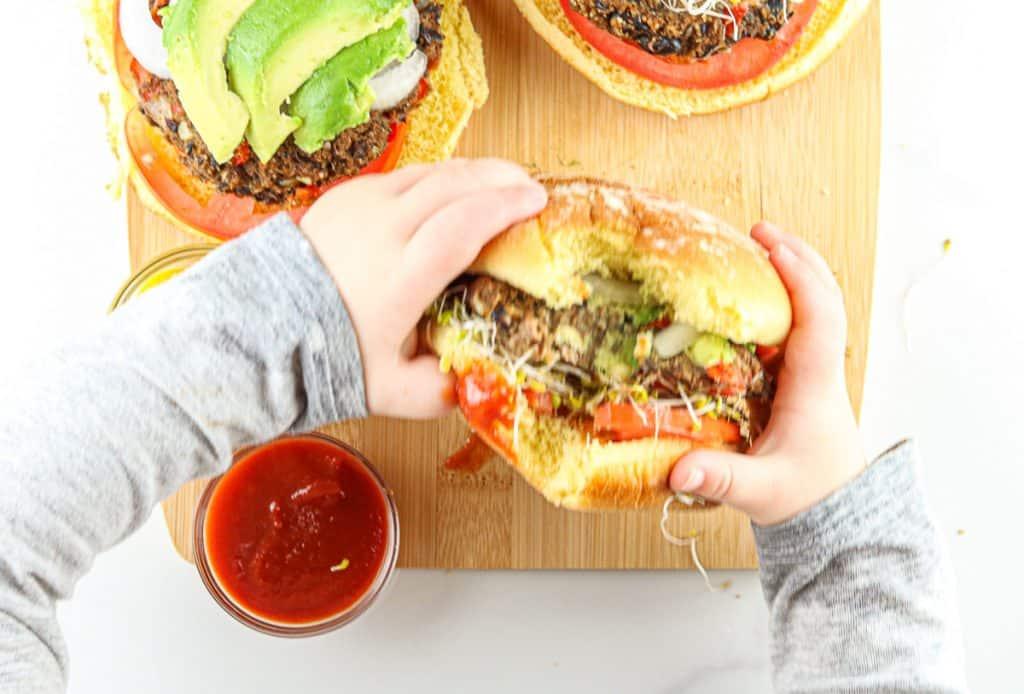 Toddler eating veggie burger.