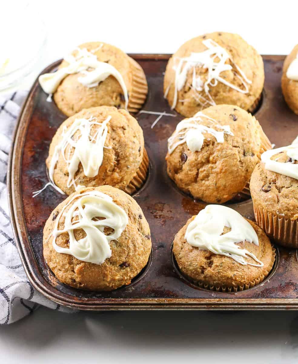 Sweet potato chia chocolate breakfast cupcakes in a muffin tin with yogurt glaze drizzled on top.