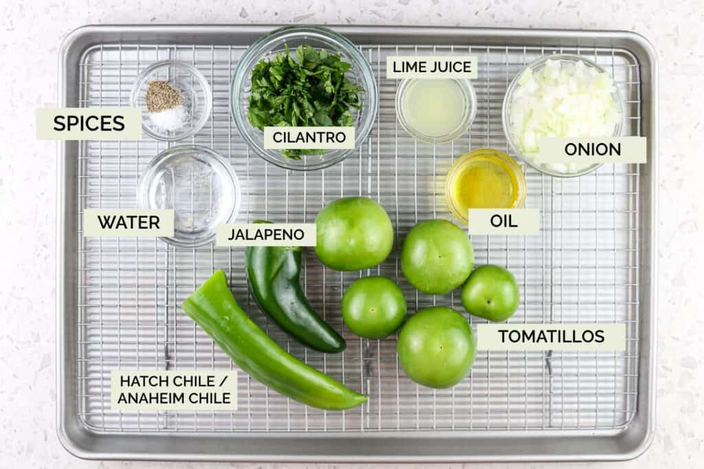 Silver baking sheet with green peppers, tomatoes, spices, and onion on top to make salsa verde.