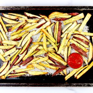 Image of French fries on a baking sheet with ketchup.