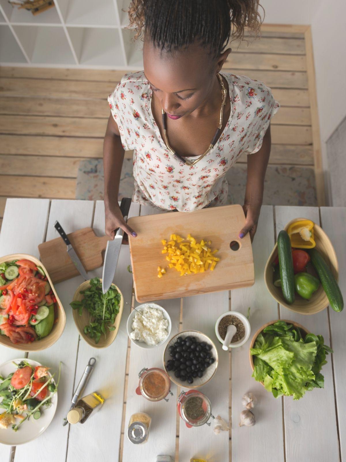 Women cutting vegetables in kitchen.
