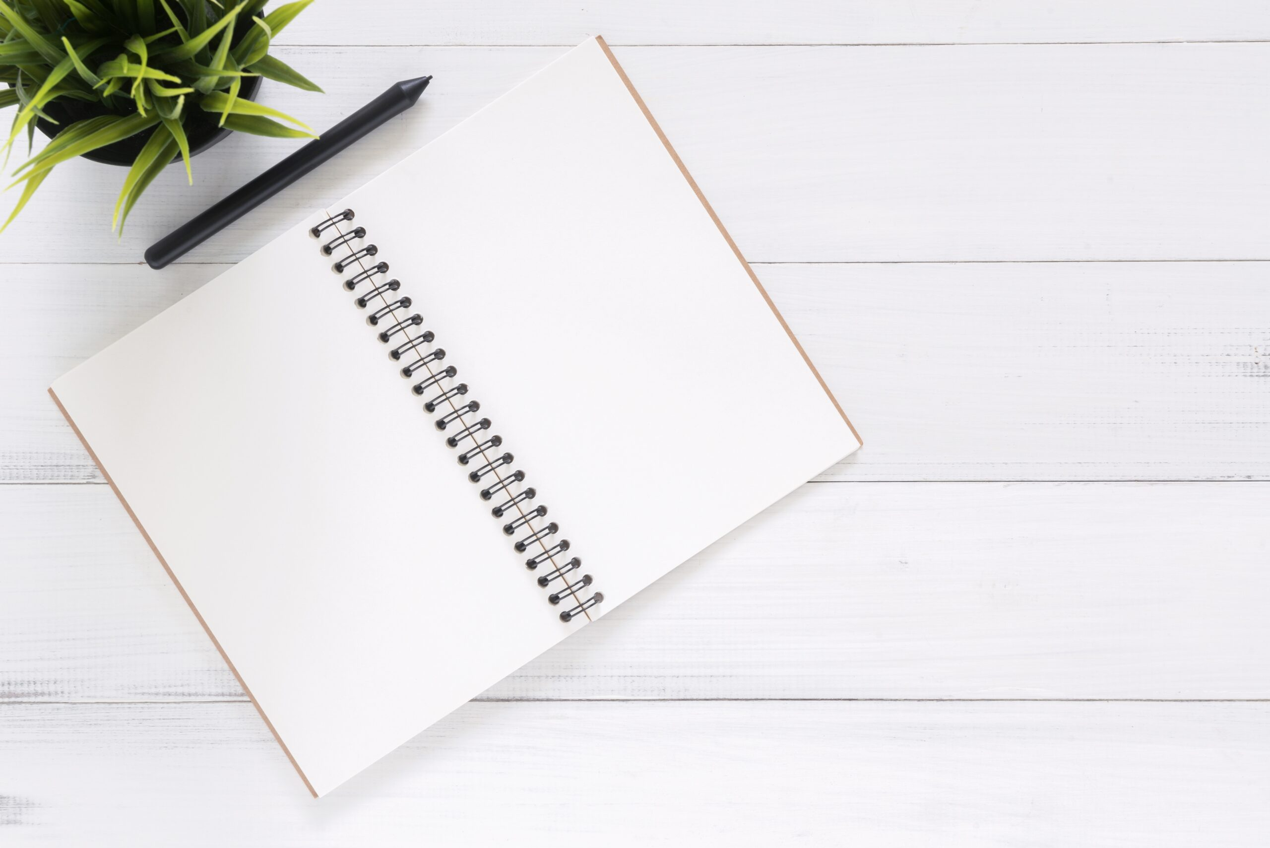 Notepad on white backdrop with pen on top.