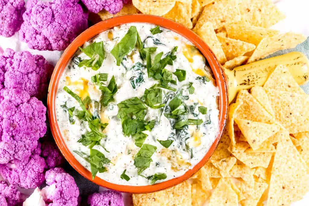 Image of plated spinach dip with chips and cauliflower around it.