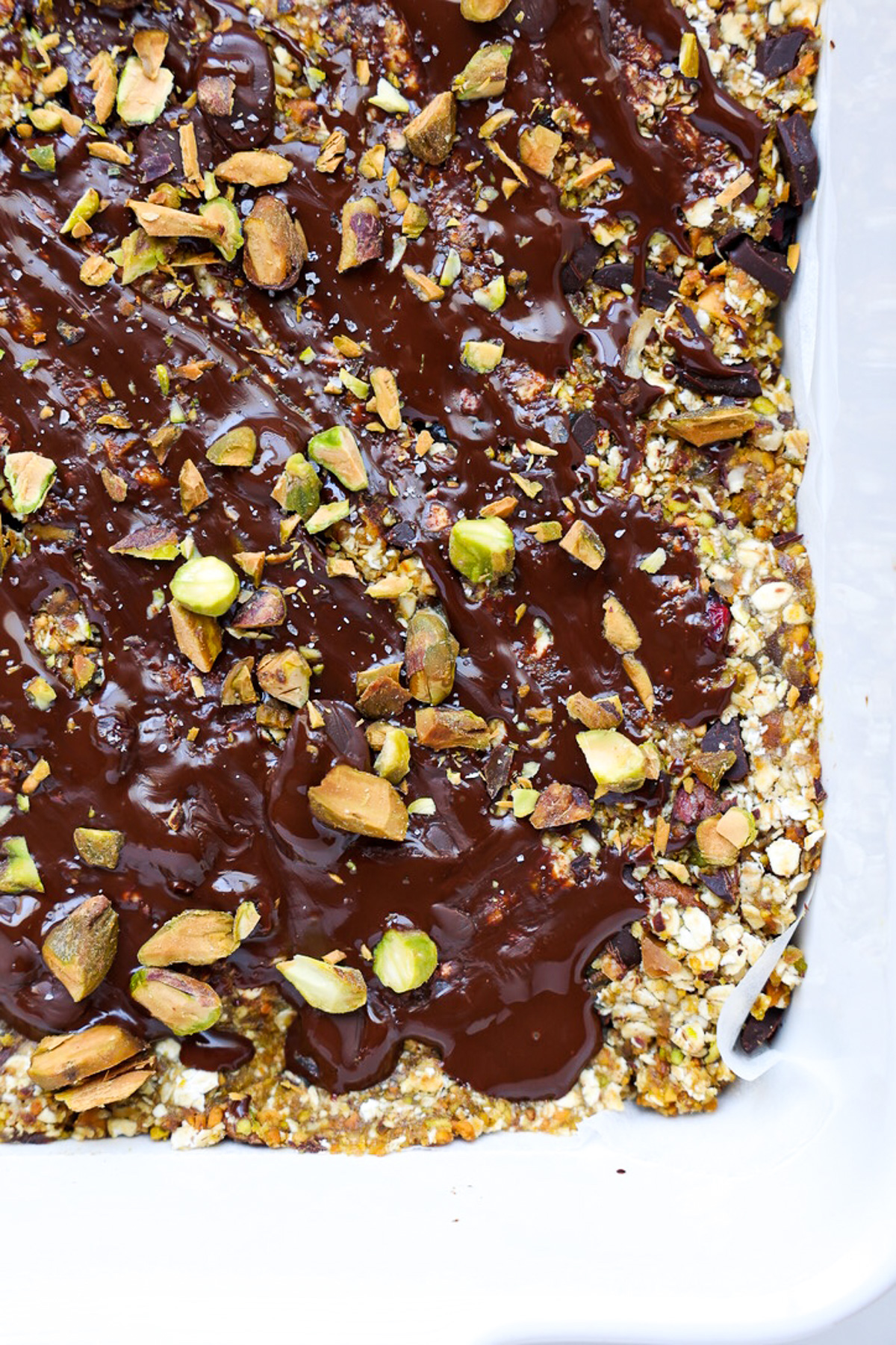 Chocolate covered no bake pistachio snack bars in white square container.