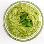 Image of walnut pesto sauce with basil on top.