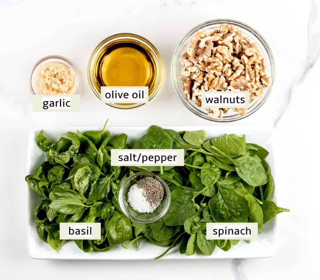 Image of ingredients needed to make walnut pesto sauce.