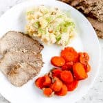 White plate with round roast, carrots and mashed potatoes.