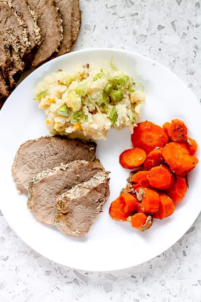 Long image of dinner plate with round roast, carrots and mashed potatoes.