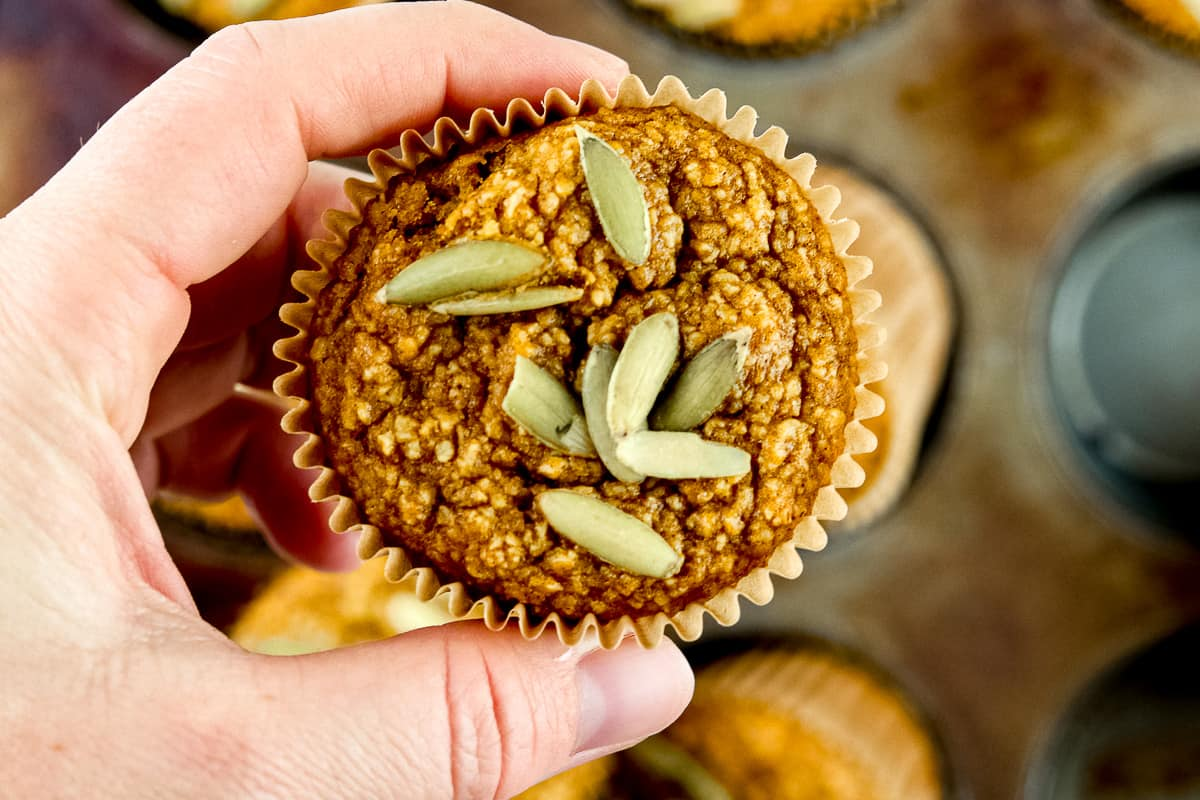 Holding a single muffin with pumpkin seeds on top.
