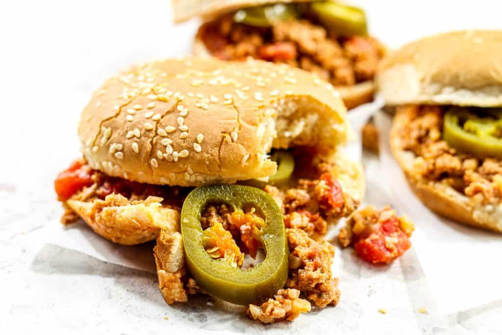 Picture of sloppy joes in a bun with jalapenos coming out.