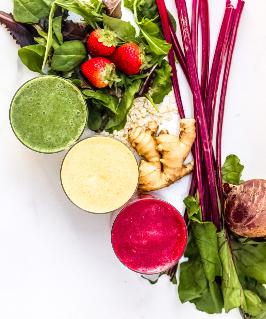White backdrop with three smoothies and beet greens.