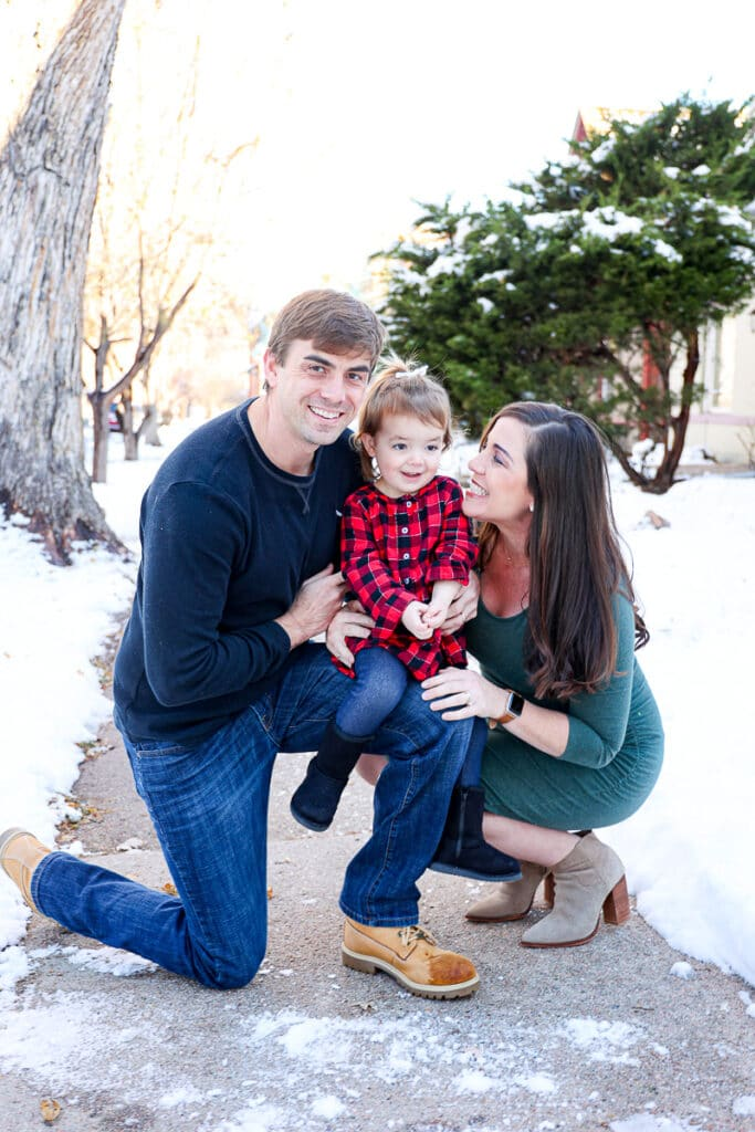 Husband, daughter and pregnancy wife kneeling and smiling in front of snow backdrop for holiday photos.