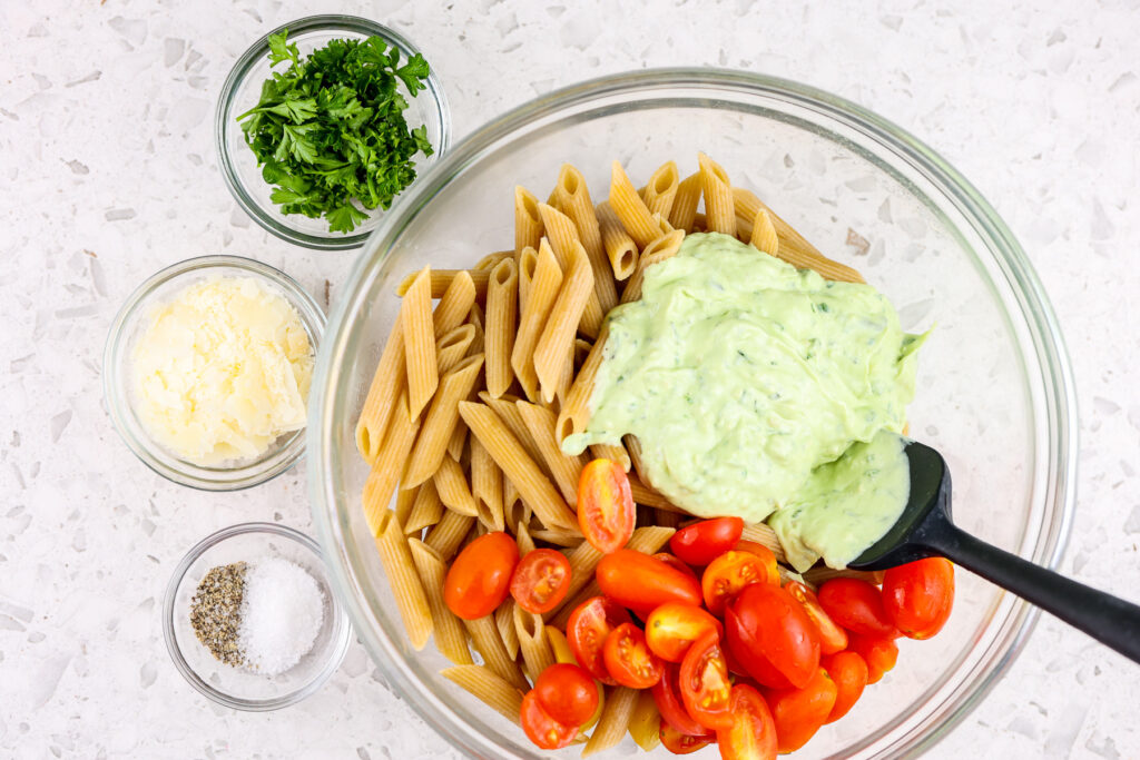 White tile backdrop with glass bowl filled with wheat pasta, red tomatoes, green sauce, and cheese, parsley and salt on the side.