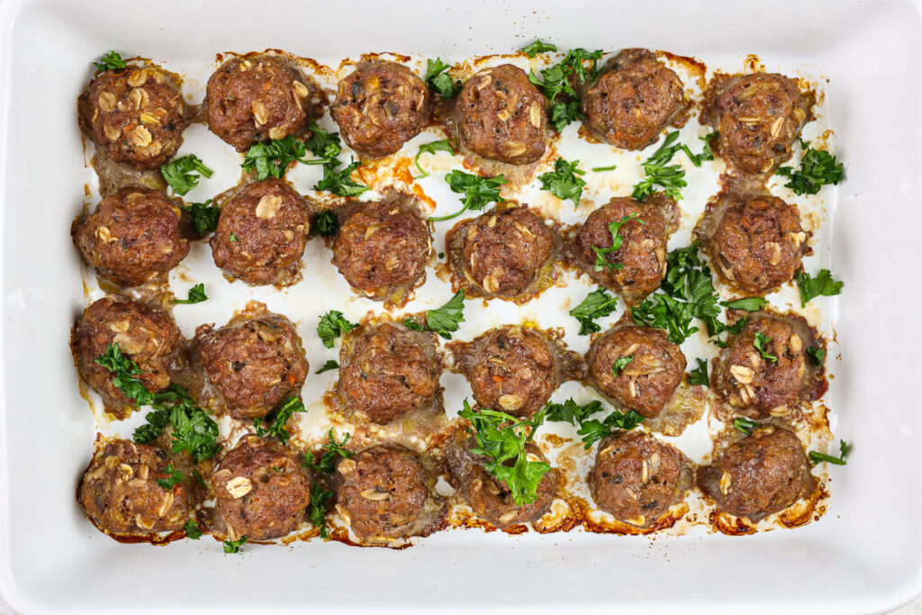 Baby meatballs lined in a white 9x13 inch pan.