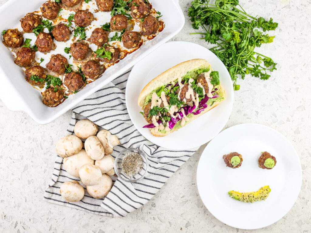 Baby meatballs in white casserole dish on the side with a hoagie roll stuffed with meatballs and greens in the center and a smiley face plate on the side with two meatballs for eyes and avocado mouth.