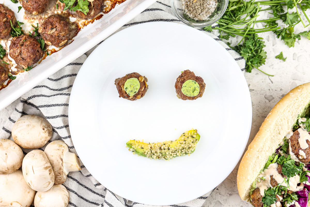 Picture of white plate with smiley face made out of two meatballs for eyes topped with green sauce and an avocado slice for a mouth.