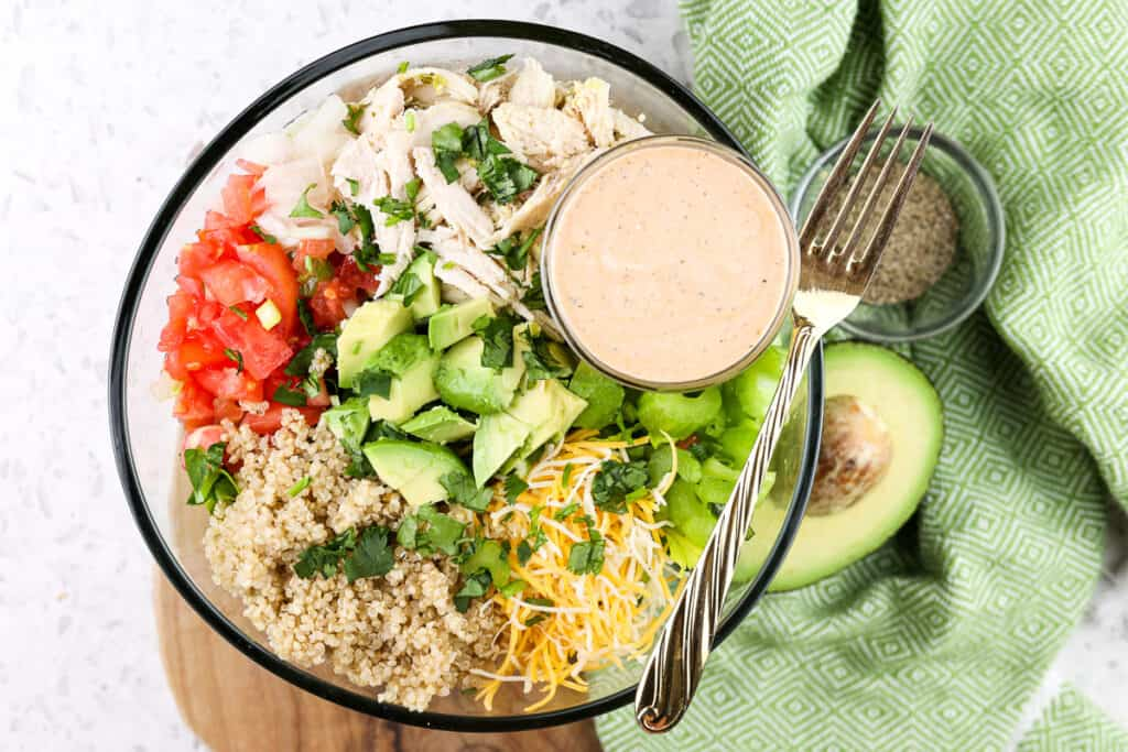 Picture of example bowl using shredded chicken with chopped veggies, a bowl of orange dressing and avocado on the side.