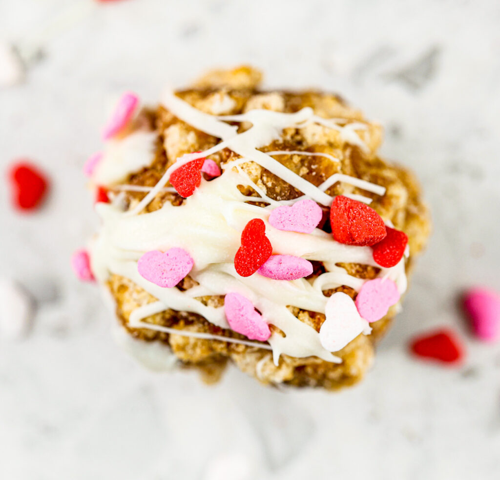 White marble tile with brown cereal cake pop with white drizzle icing and red and pink heart sprinkles on top.