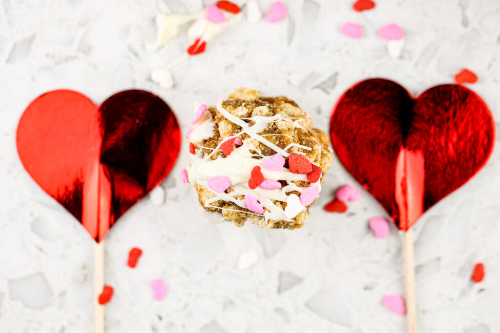 White marble backdrop with cereal cake pop and two hearts on the side.
