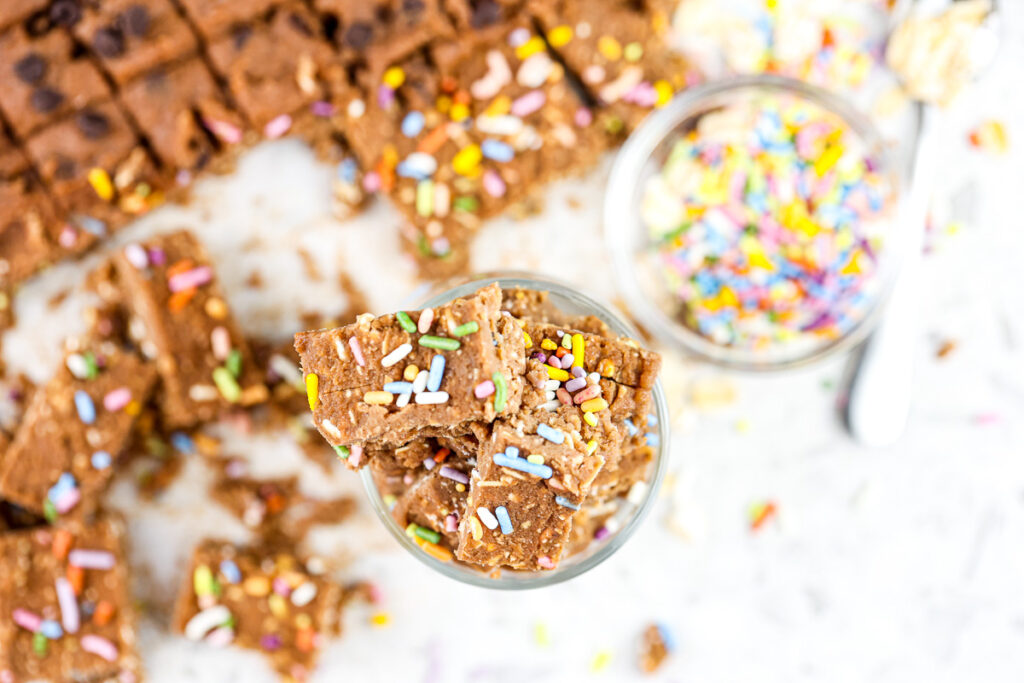 White backdrop with light brown chickpea cookie dough with rainbow sprinkles on top.