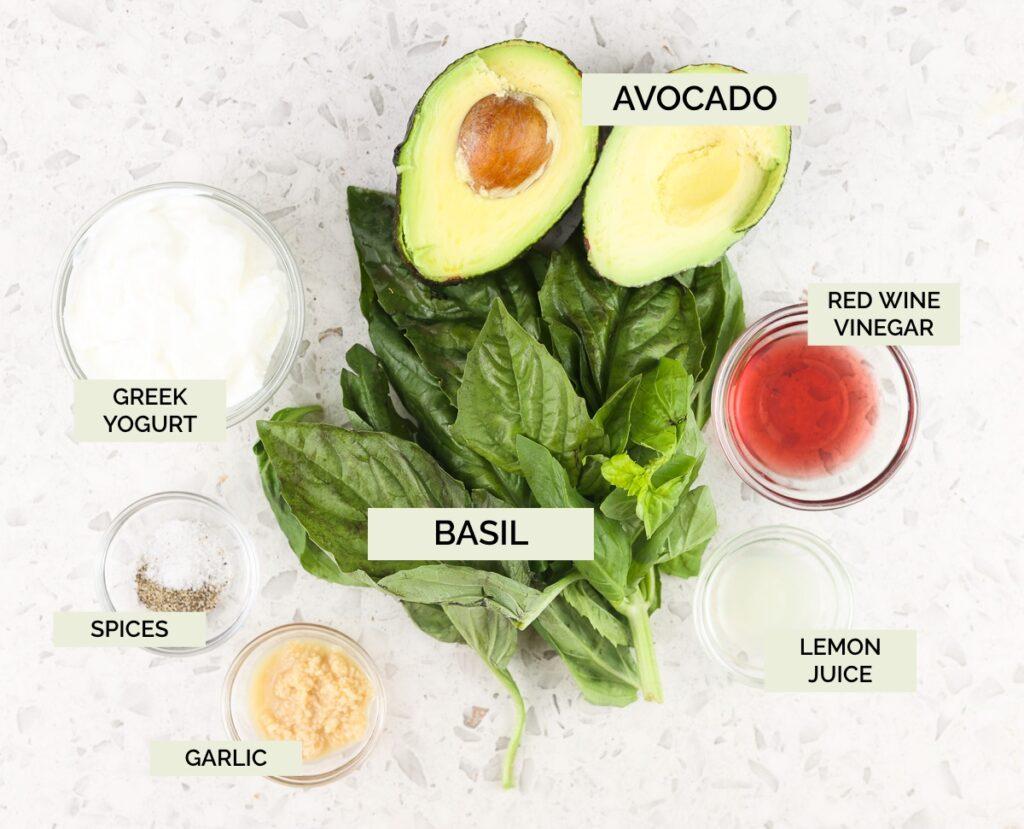 White tile backdrop with fresh green basil, avocado, and spices on top to make Avocado Pesto Pasta.