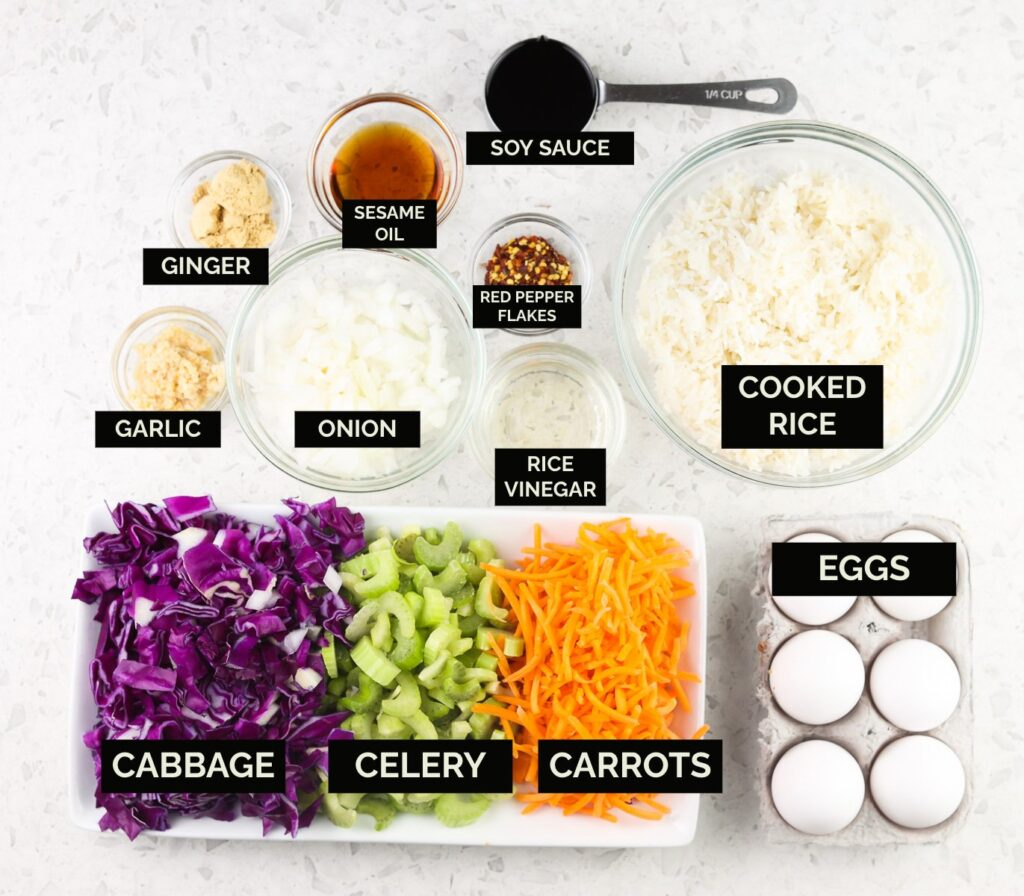 White tile with bowls on top featuring eggs, colorful purple, orange, and green veggies alongside rice and seasoning with black text boxes identifying the ingredients.