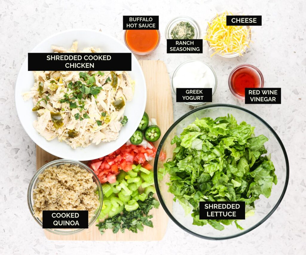 White tile with bowls of shredded chicken, lettuce, veggies, and sauces to make Buffalo Chicken Grain Bowls.
