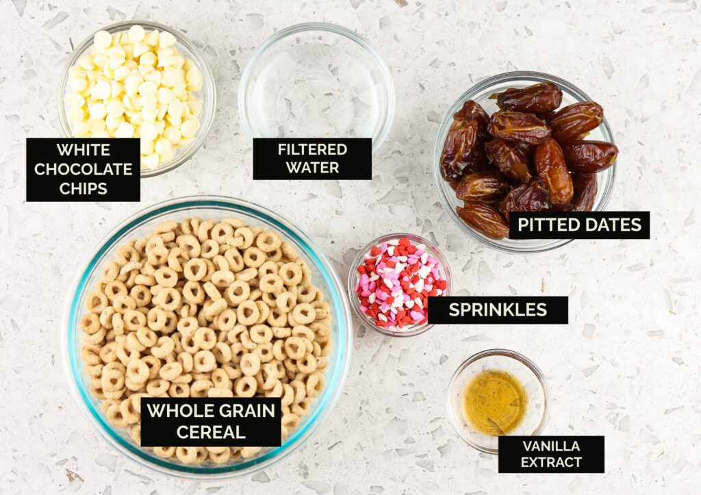 White marble backdrop with glass bowls of ingredients, including brown colored cheerios, chocolate chips, sprinkles, and dates to make Cereal Cake Pops.