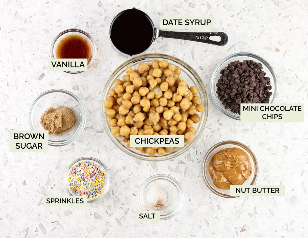White backdrop with clear glass bowls of ingredients on top with text overlay. Ingredient bowls are filled with chickpeas, date syrup, nut butter, spices, and chocolate chips.