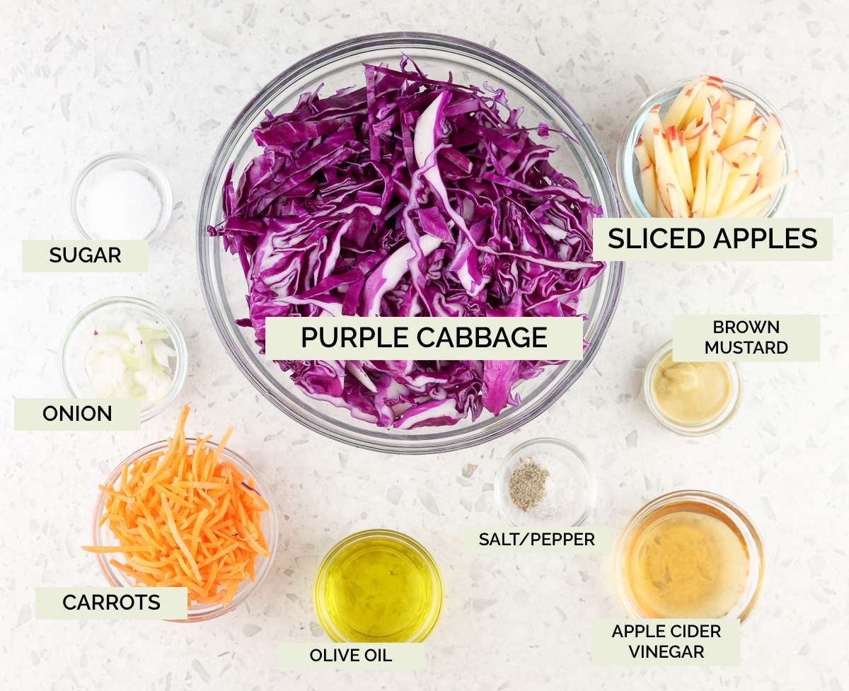 White marble backdrop with glass bowls filled with purple cabbage, vinegars, and carrots.