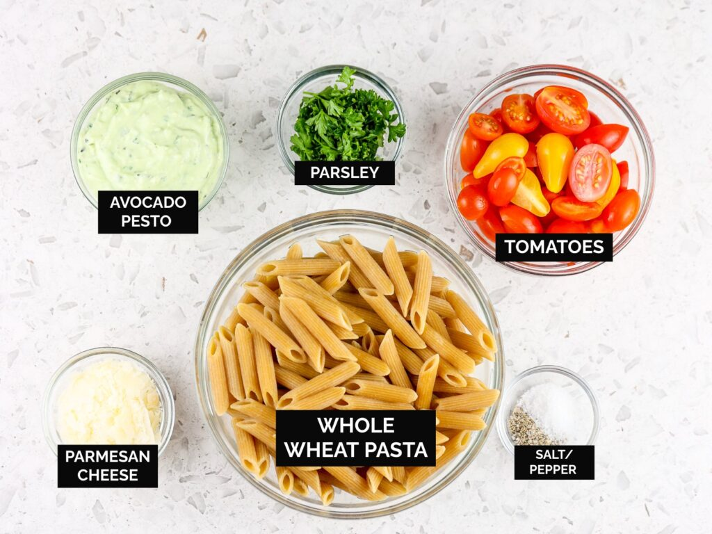 White tile backdrop with brown wheat pasta, cheese, tomatoes, and green pesto in glass bowls.