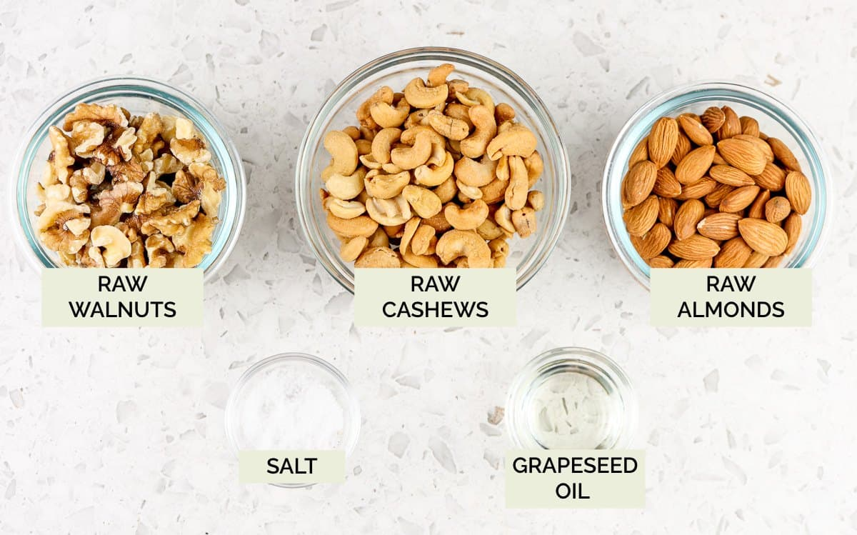 White backdrop with 3 glass bowls of nuts with green text overlay to show how to make roasted mixed nuts.