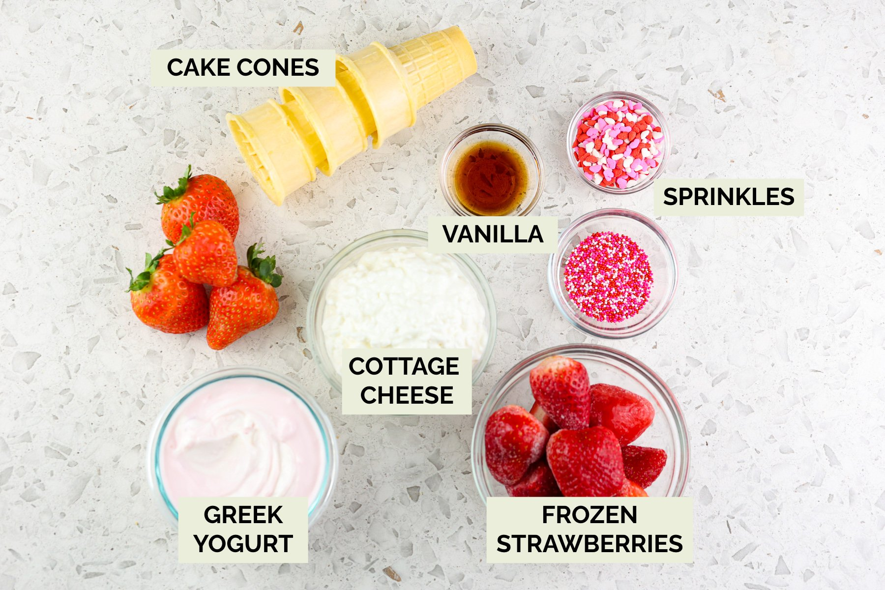 White backdrop with glass bowls on top filled with cottage cheese, berries, sprinkles and yellow cake cones .
