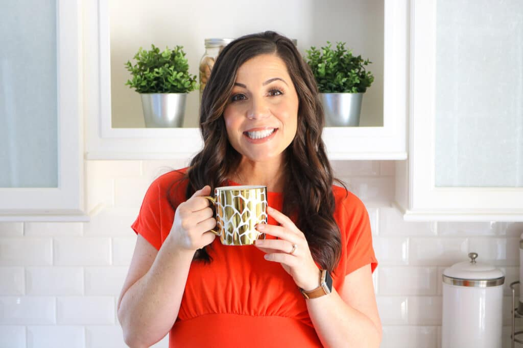 Headshot of Liz Shaw on About Me page holding a gold mug and wearing a red dress.