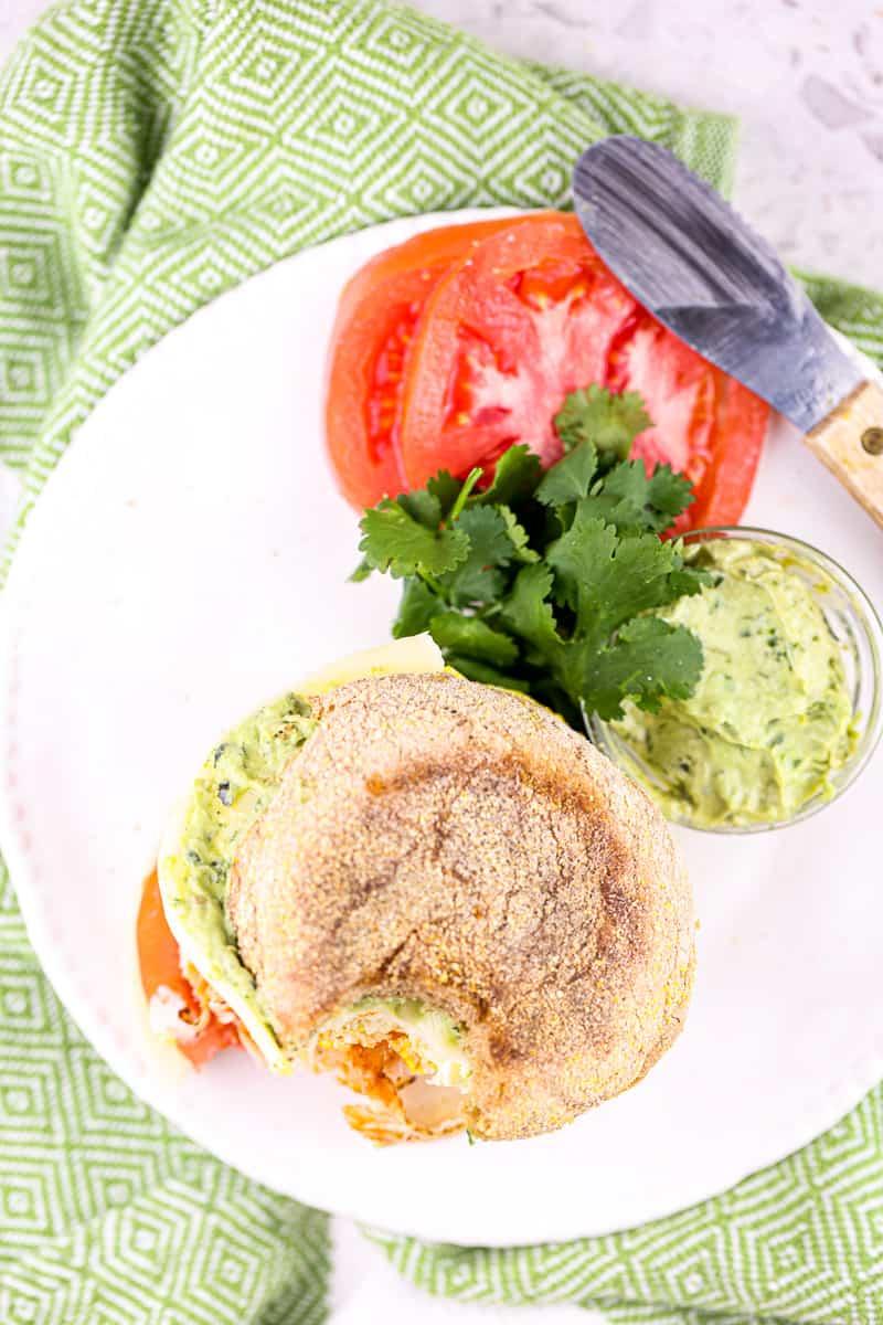 Green napkin underneath white plate with brown English Muffin and tomato, pesto and cilantro garnish.