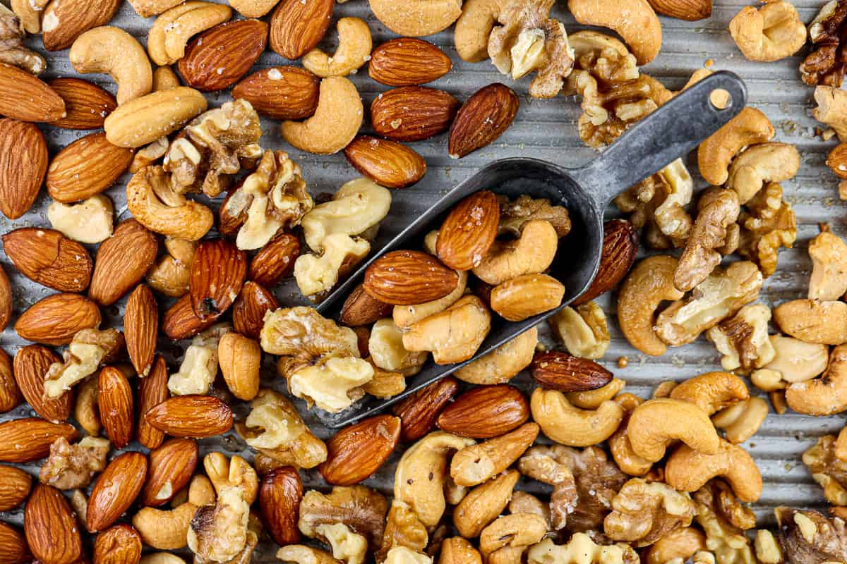 Silver baking sheet covered with roasted cashews, almonds and walnuts with a metal serving handle in the center.