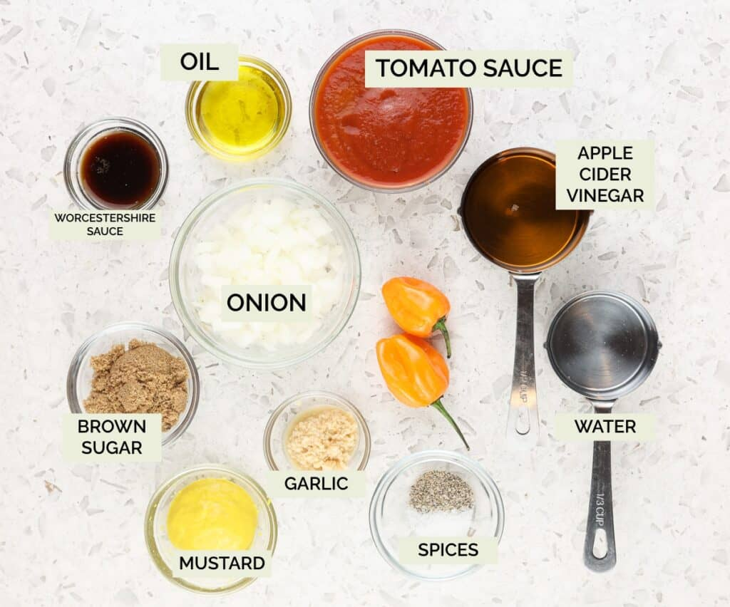 White marble backdrop with ingredients in clear bowls like onions, tomatoes, and spices to make sauce.