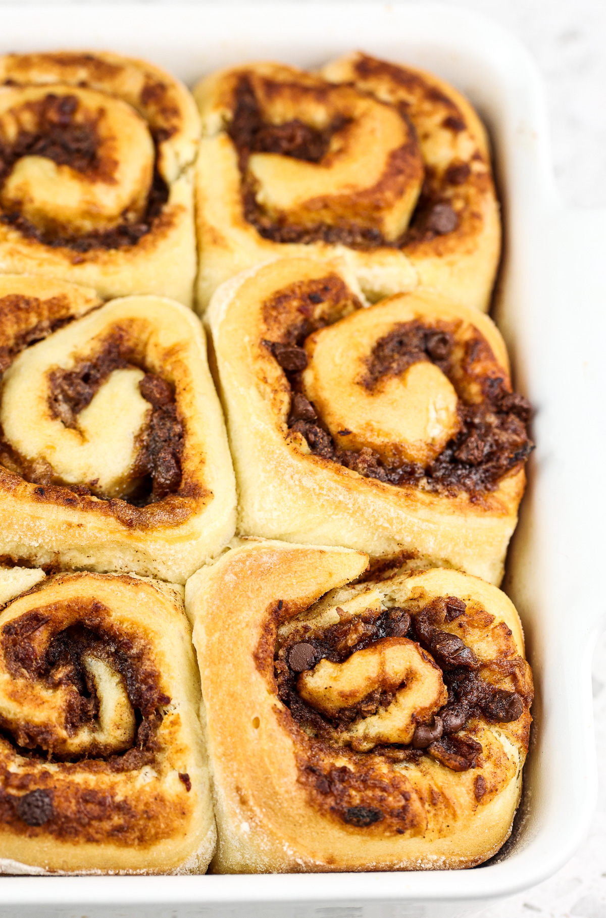 Brown Cinnamon Rolls in a white baking dish with a brown date filling peaking out.