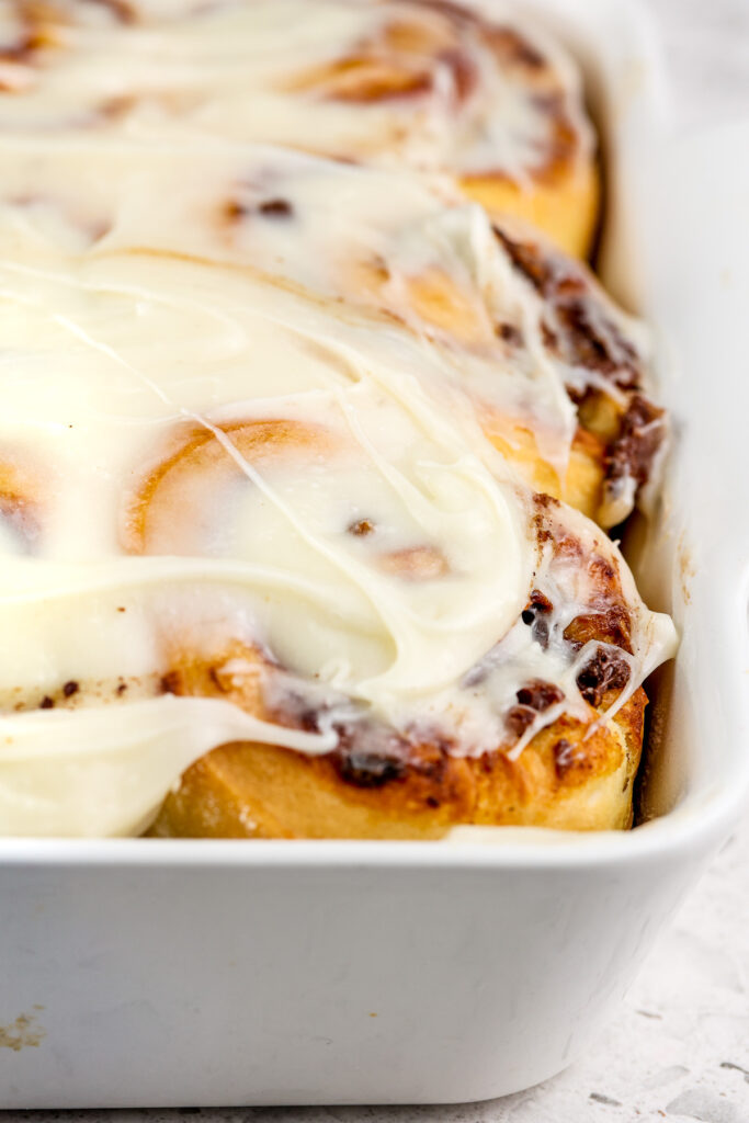 Brown Cinnamon Rolls in a white baking dish with a brown date filling peaking out and white frosting on top.