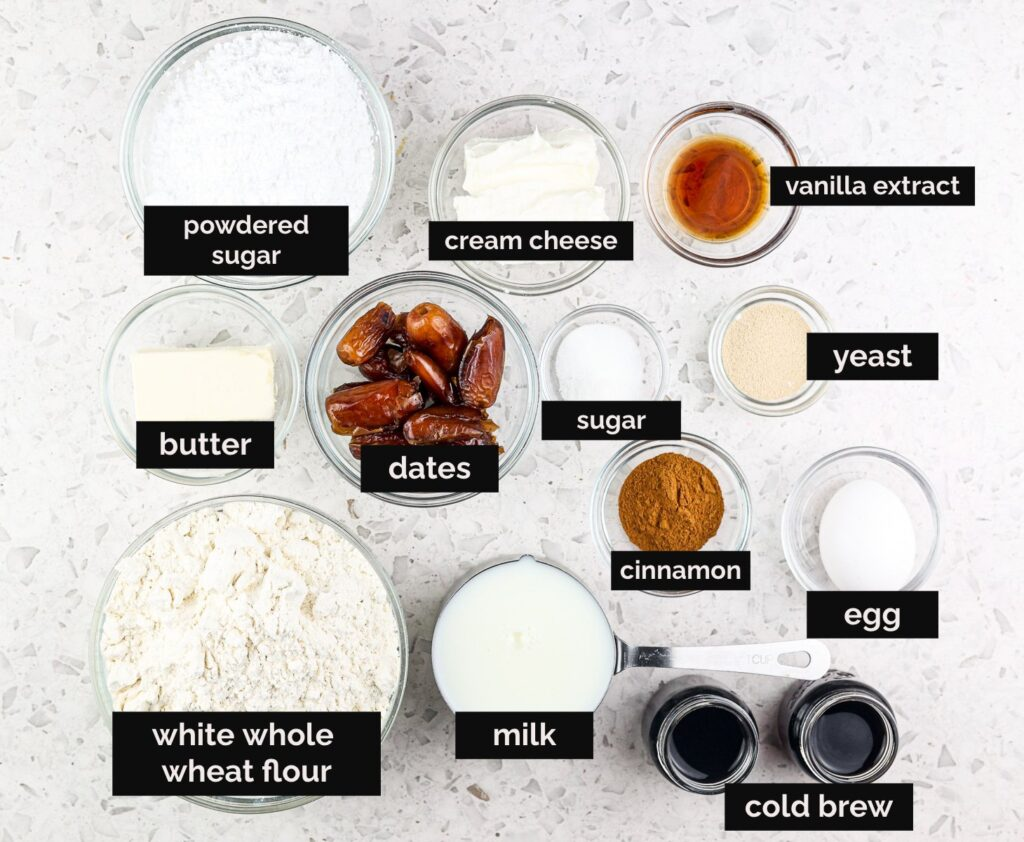 White tile backdrop with black text boxes on top of glass bowls holding ingredients to make baked cinnamon rolls. Flours, egg, dates, coffee, spices, and sugar are presented.